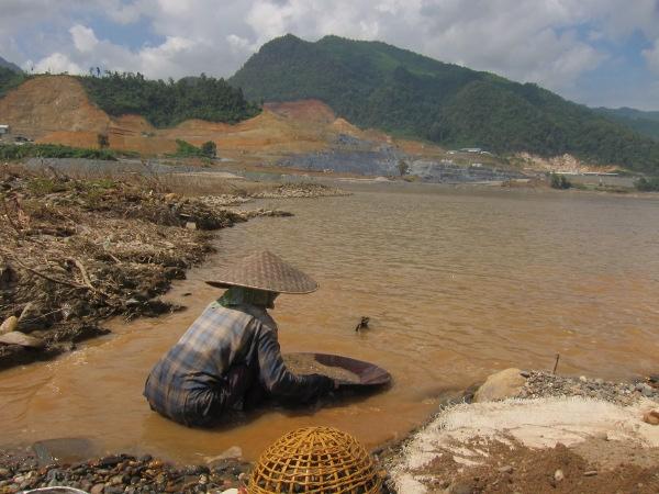 Eine Frau beim Goldwaschen am Mekong, im Hintergrund die Xayaburi-Baustelle (Dezember 2012). Die Frau ist mittlerweile mit großer Wahrscheinlichkeit zwangsumgesiedelt worden. (Print-Version auf Anfrage)